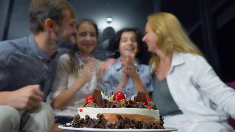 Candele di salto sorridenti felici del ragazzo sulla sua torta di compleanno bambini circondati dalla loro famiglia Torta di comp fotografie stock libere da diritti