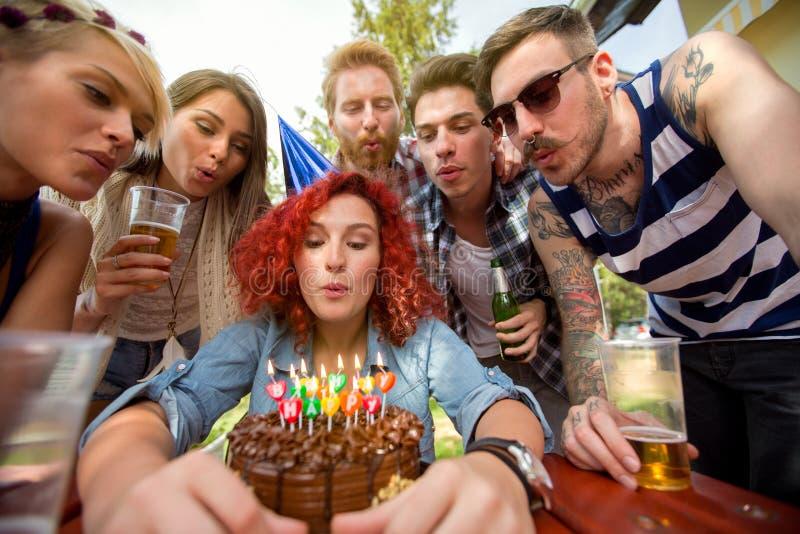Candele di salto sulla torta di compleanno del cioccolato immagine stock