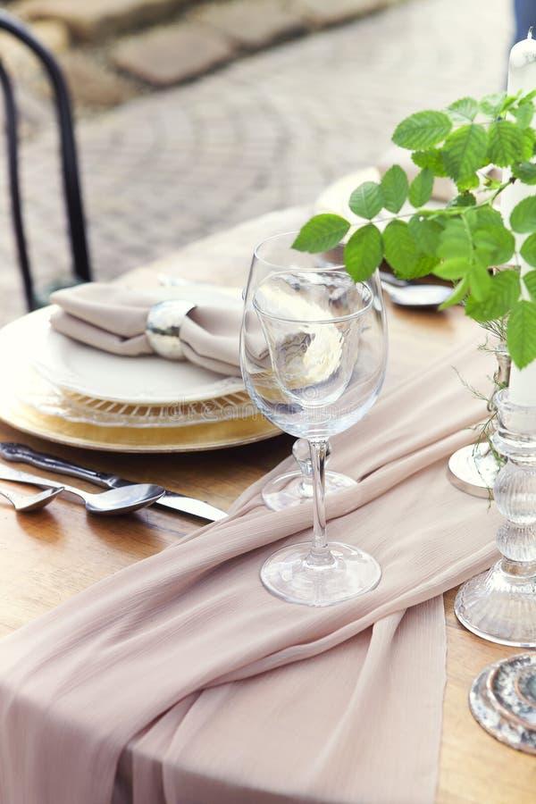 Candele e vaso con rose bianche disposte su una tavola rotonda vicino a dei melassi immagine stock libera da diritti