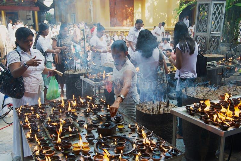 Candele leggere della gente al tempio buddista durante la celebrazione religiosa di Vesak a Colombo, Sri Lanka immagine stock libera da diritti