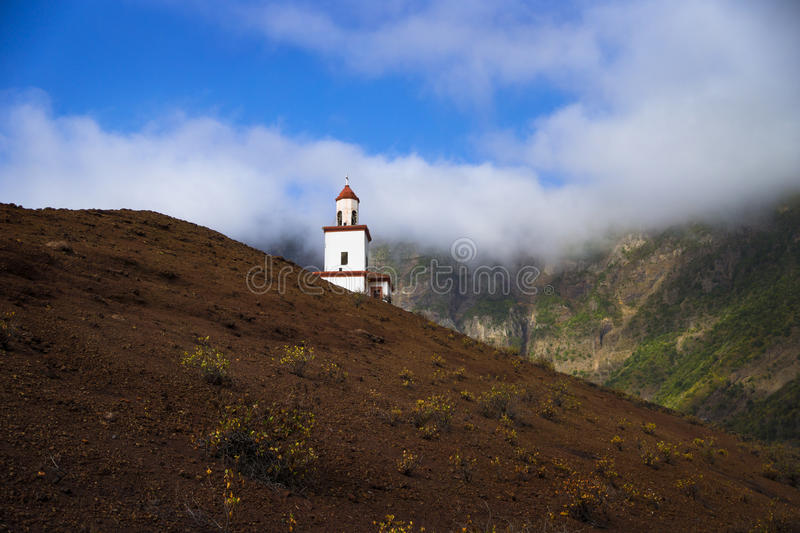 Candeleria Chapel in Valverde in Frontera with green hills and m. Ist, clouds, blue sky stock image