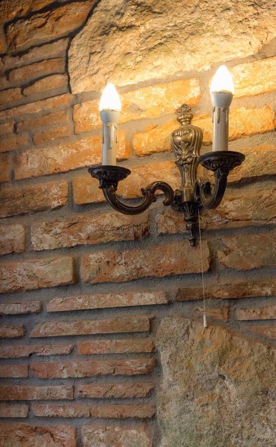 Candeliere con la lampada sul muro di mattoni in costruzione antica Interno medievale Vecchia casa del mattone e della pietra fotografie stock libere da diritti