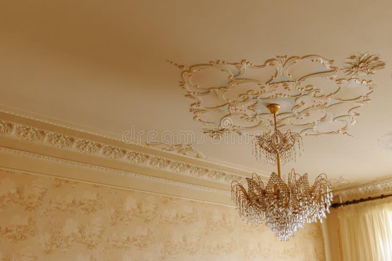 Candeliere a cristallo con oro su un soffitto bianco con il retro stucco fotografie stock