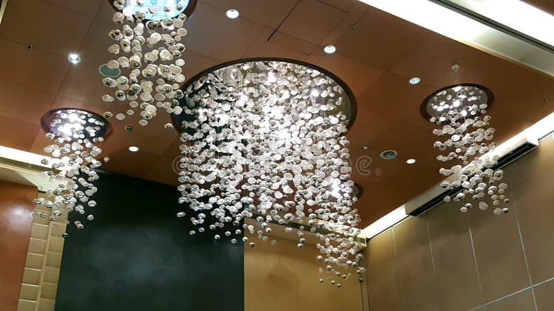 Candeliere a cristallo rotondo che pende dal soffitto di un corridoio fotografia stock