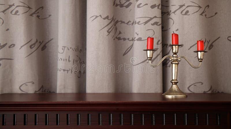 Candeliere e tre candele rosse fotografie stock