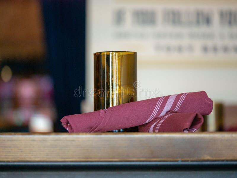 Candeliere ed utensili avvolti in tovagliolo porpora che si siede su una tavola del ristorante immagini stock