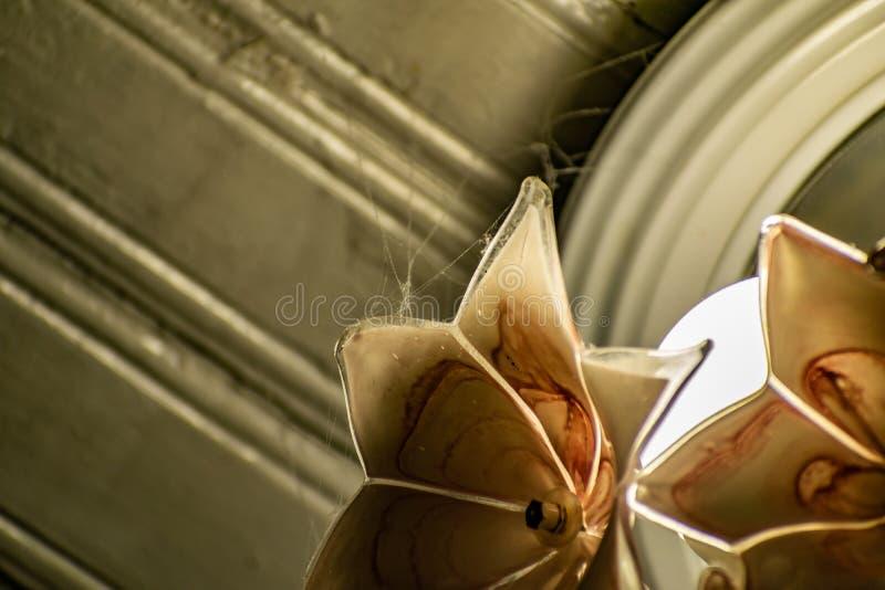 Candeliere rosa di vetro sotto forma di mazzo del fiore sui precedenti della struttura del soffitto di legno bianco e vecchio spo immagini stock libere da diritti