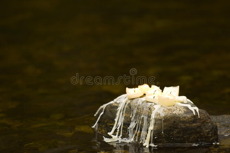 Candels que senta-se na rocha com decorações do Natal foto de stock royalty free