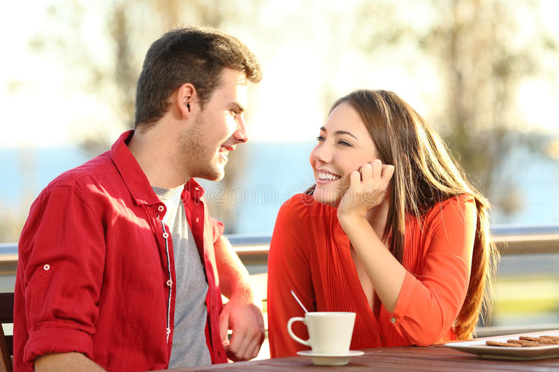 Candid couple in love flirting in a terrace. Candid couple date falling in love flirting in a terrace looking each other with tenderness thinking to kiss stock image