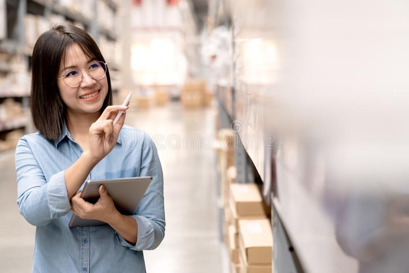 Candid or headshot of young happy attractive asian employee or staff working in store inventory in warehouse using computer tablet stock photo
