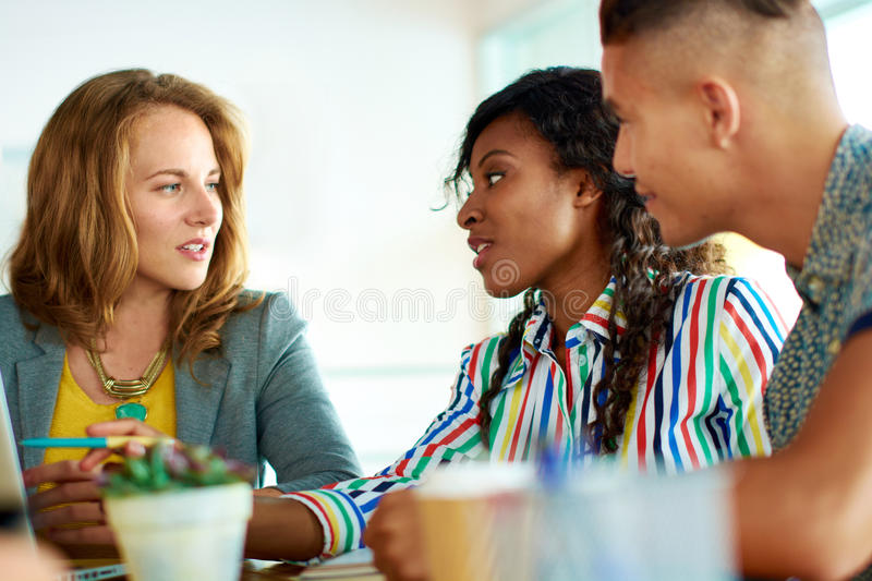 Candid image of a group with succesful business people caught in an animated brainstorming meeting royalty free stock photos