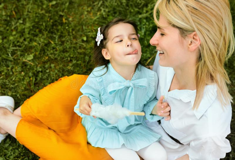 Candid image of happy mother playing with her daughter outdoors. Cute little girl eating cotton candy with her mom, royalty free stock photo