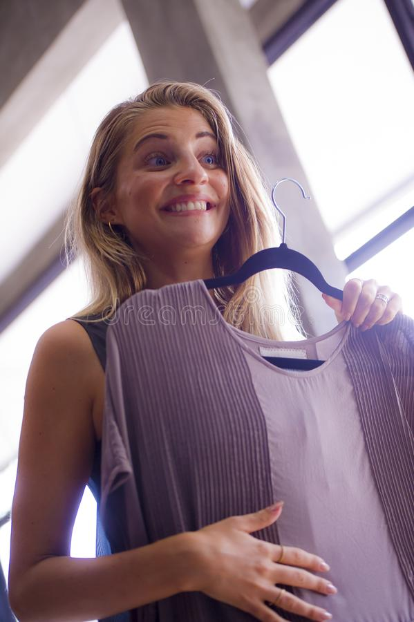 Candid lifestyle portrait of young beautiful and happy blond woman enjoying shopping trying out sweet dress at vintage and cool be royalty free stock photos