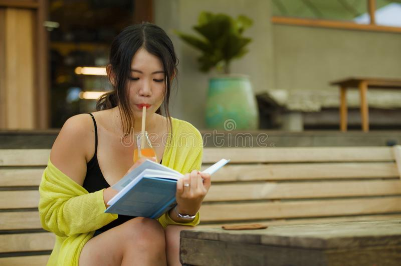 Candid lifestyle portrait of young beautiful and relaxed Asian Korean student girl on reading book or studying outdoors at coffee royalty free stock image