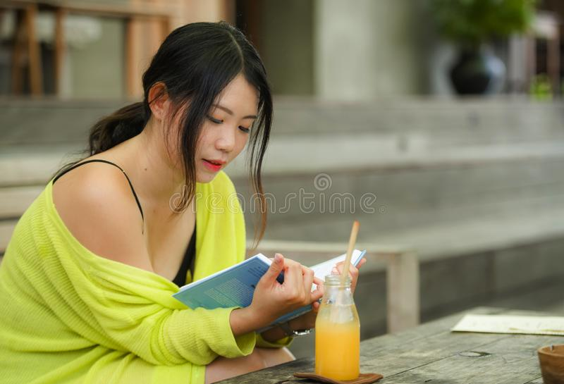 Candid lifestyle portrait of young beautiful and relaxed Asian Korean student girl on reading book or studying outdoors at coffee stock image