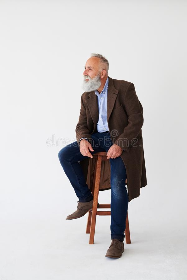 Candid mature bearded man in coat sitting on chair in studio royalty free stock images
