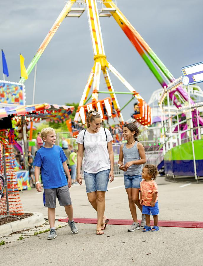Smiling family having fun at an outdoor summer carnival. Candid photo of a smiling family group having fun at an outdoor carnival or theme park. Full length royalty free stock images