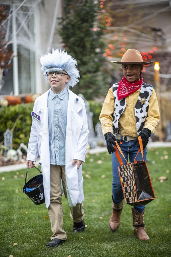 Group of Kids Trick or Treating on Halloween in a decorated neighborhood stock photo