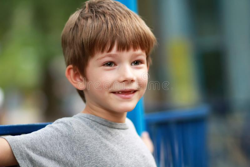 Candid portrait of a happy boy in grey t shirt smiling and sitting on the bench outdoor in the park whose front top milk teeth out. Candid portrait of a happy royalty free stock image