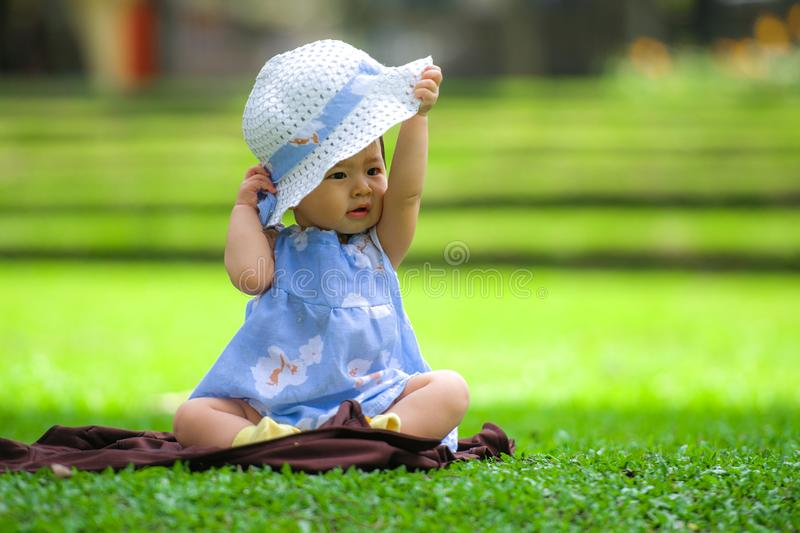 candid portrait of sweet and adorable Asian Korean baby girl 3 or 4 months old playing with hat alone at city park royalty free stock photo