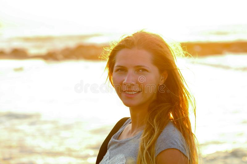 Candid portrait of young woman by the sea at sunset, strong sun backlight, background overexposed intentionally for atmosphere stock images