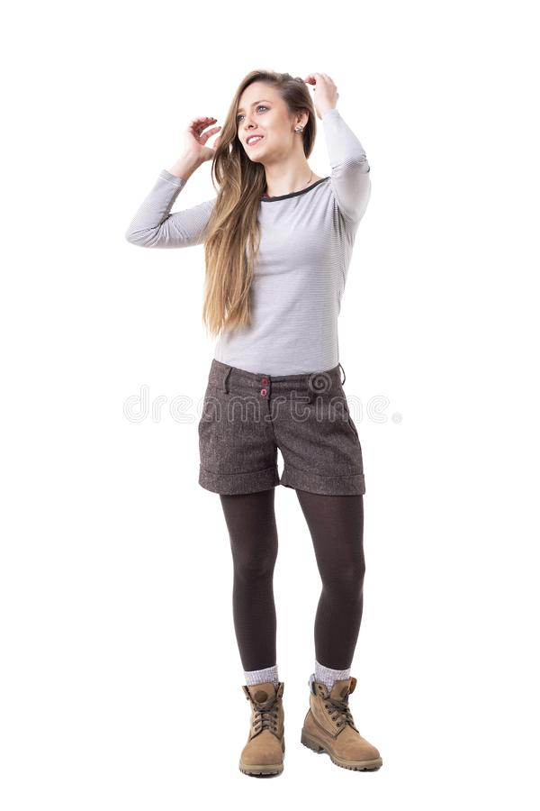 Candid relaxed happy long hair blonde woman looking up adjusting hair. royalty free stock image