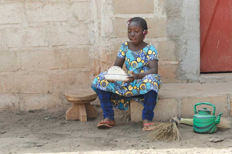 Candid Shot of African Black Girl Cooking Rice Outdoors stock photo
