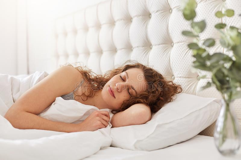Candid shot of pleased young woman enjoys good sleep in bedroom, lies in comfortable bed, has appealing appearance, keeps eyes cl stock photography