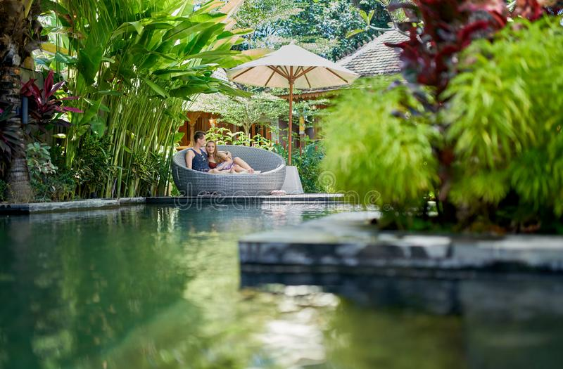 Candid shot of young caucasian couple lounging in modern chair near luxurious pool of tropical hotel and spa in Bali. Natural shot of caucasian man and woman royalty free stock images