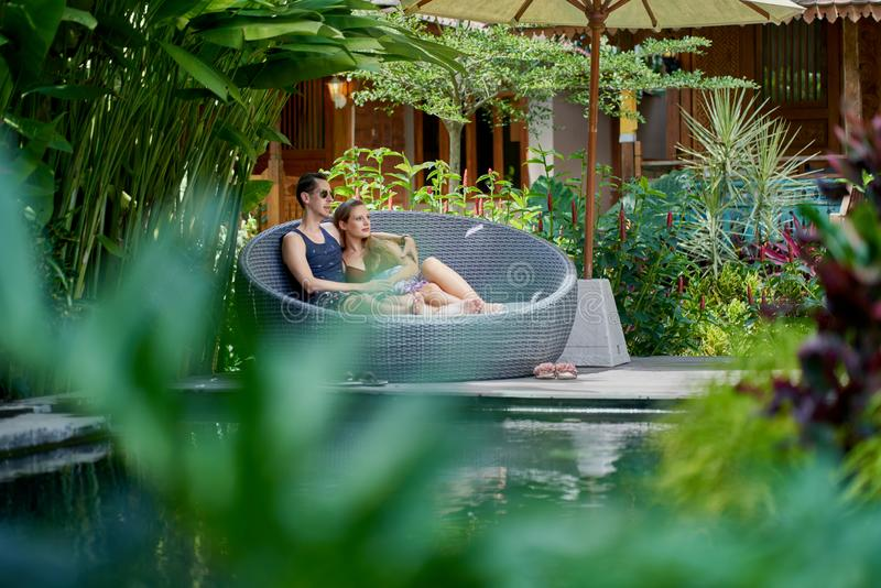 Candid shot of young caucasian couple lounging in modern chair near luxurious pool of tropical hotel and spa in Bali royalty free stock image
