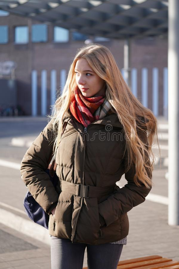 Candid street style image of young woman waiting at bus station royalty free stock image