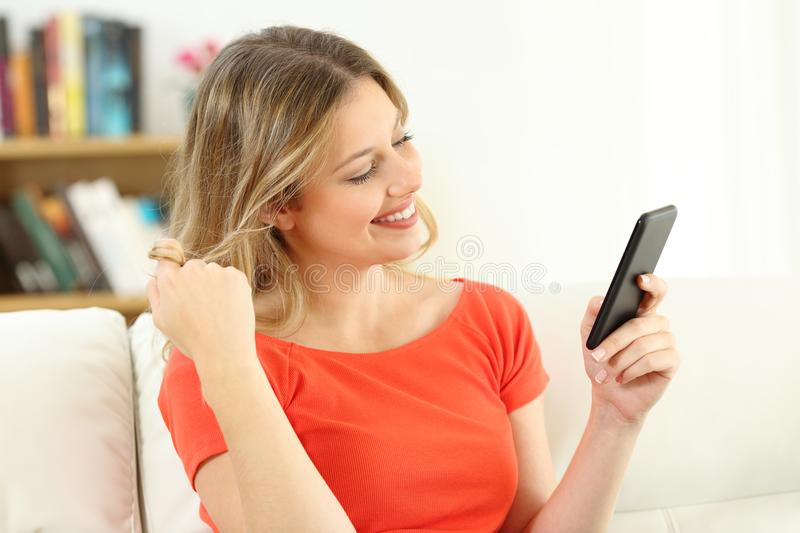 Candid woman flirting dating on line with a phone. Candid woman flirting and dating on line with a smart phone sitting on a couch in the living room at home stock images