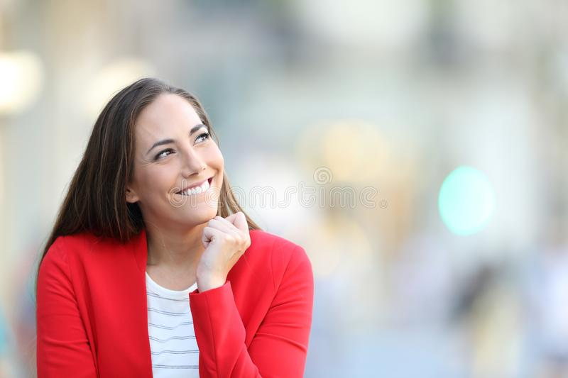 Candid woman thinking looking at side in the street royalty free stock photography