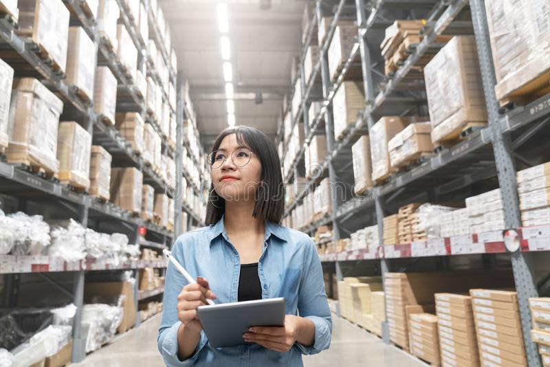 Candid of young attractive asian woman auditor or trainee staff work looking up stocktaking inventory in warehouse store by stock photography