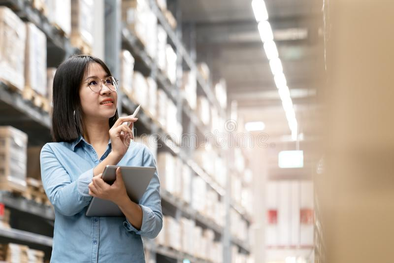 Candid of young attractive asian woman, auditor or trainee staff working in warehouse store counting or stocktaking inventory by stock image