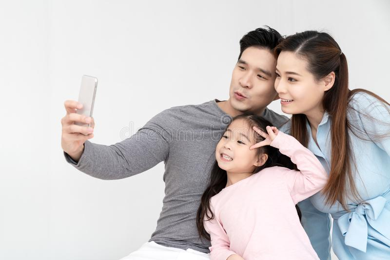 Candid of young attractive happy asian family using smartphone selfie together or video call. Social media community in asian. Family using 5G digital stock images