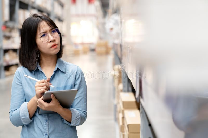 Candid young unhappy asian woman, auditor or employee feeling confused in warehouse store. Young girl puzzled face, expressing royalty free stock photography