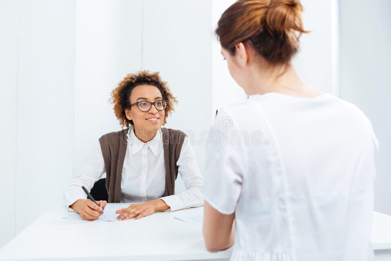 Candidat de entrevue de femme d'affaires heureuse d'afro-américain s'asseyant à la table image libre de droits