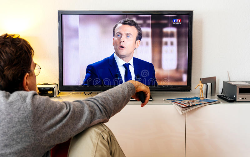 Candidate supporter watching debate between Emmanuel Macron and Marine Le Pen. PARIS, FRANCE - MAY 03, 2017: Supporter of President watch the TV debate between stock image