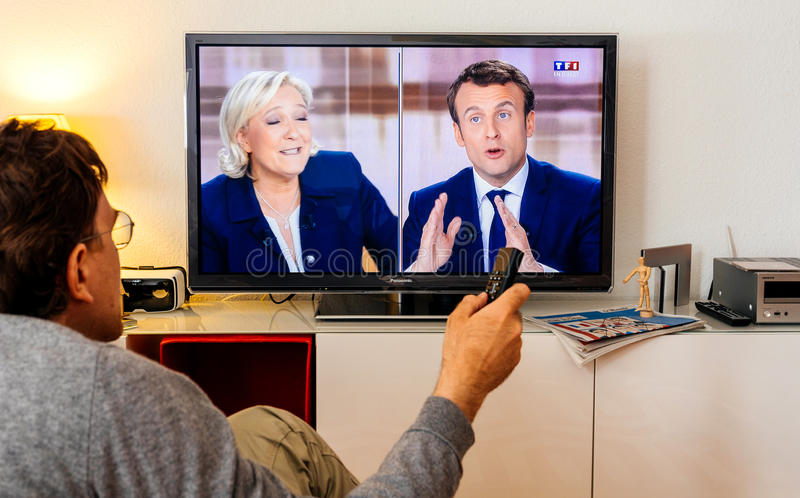Candidate supporter watching debate between Emmanuel Macron and. PARIS, FRANCE - MAY 03, 2017: Supporter of President watch the TV debate between Emmanuel Macron royalty free stock photography
