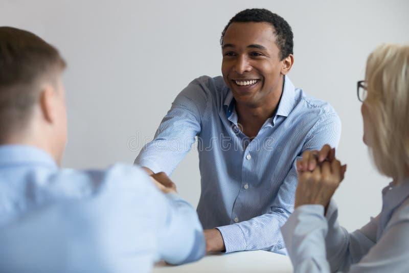 Candidato afroamericano que sacude la mano del patrón en la entrevista de trabajo imagen de archivo