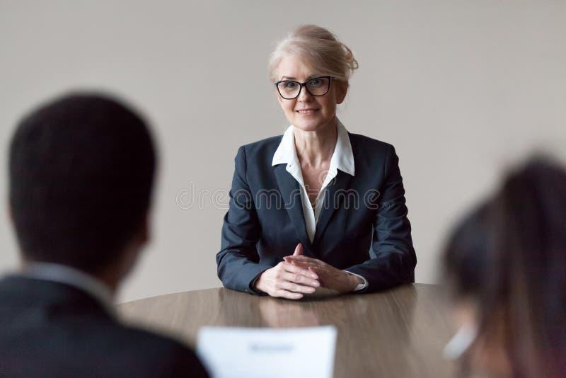 Candidato de trabajo femenino de mediana edad sonriente que hace la primera impresión en la entrevista imagen de archivo