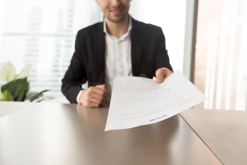 Candidato de trabajo sonriente que entrega el curriculum vitae al reclutador durante adentro imagenes de archivo