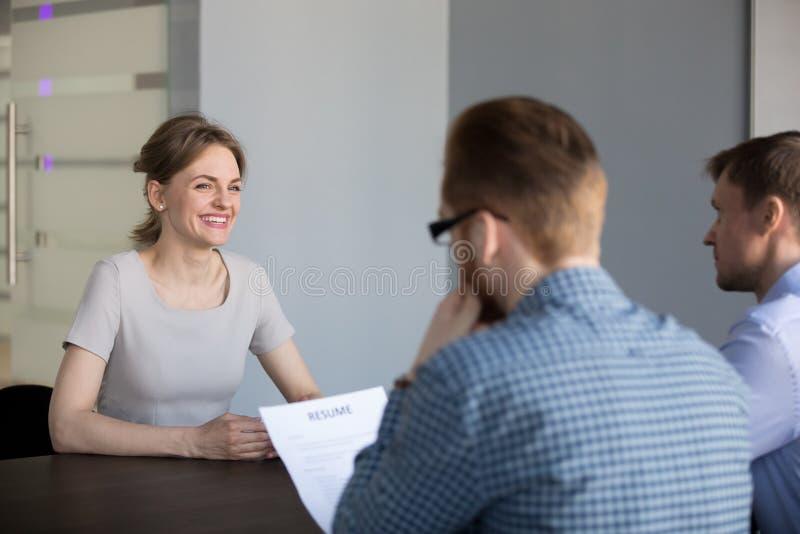 Candidato femenino confiado que sonríe durante entrevista de trabajo en offic imagen de archivo libre de regalías