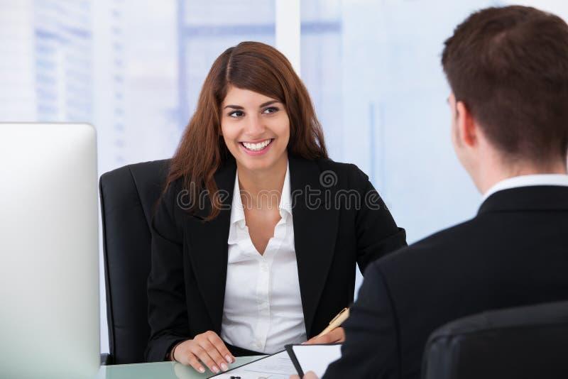 Candidato masculino de entrevista da mulher de negócios na mesa fotos de stock royalty free