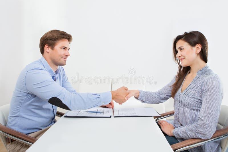 Candidato sonriente que sacude la mano con el hombre de negocios foto de archivo libre de regalías