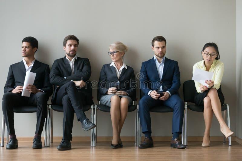 Candidatos diversos de los empresarios que se sientan en entrevista de trabajo de la fila que espera para foto de archivo libre de regalías