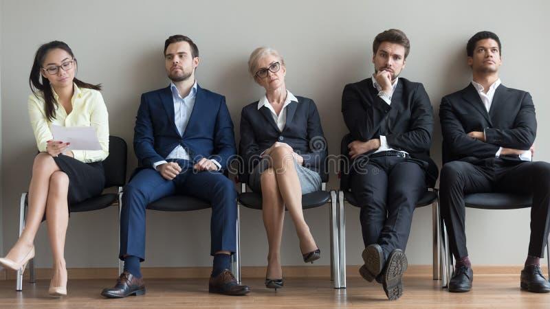 Candidatos diversos que esperam sua volta que prepara-se para a entrevista de trabalho imagem de stock