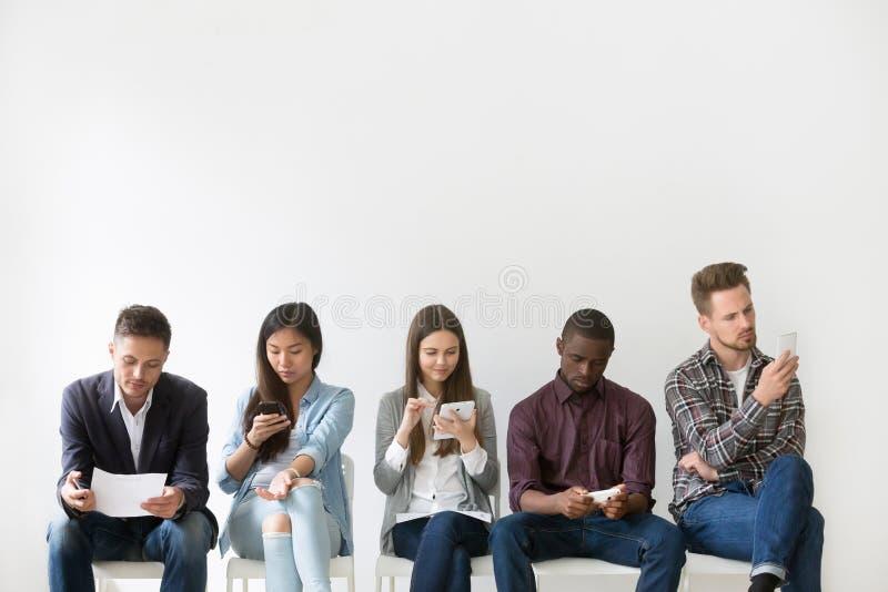 Candidatos multi-étnicos que preparam-se para a entrevista de trabalho que espera no qu imagens de stock