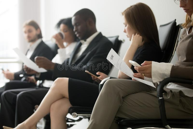 candidatos Multi-étnicos que sentam-se no intervi de espera do trabalho da fila imagem de stock royalty free